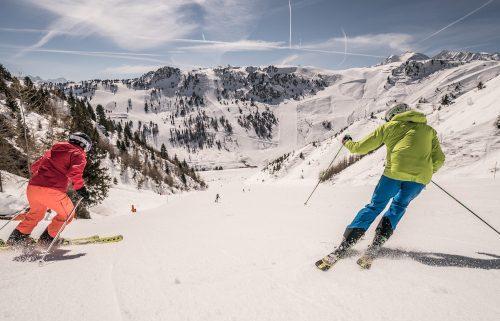 Mann und Frau beim Skifahren im Sonnenschein